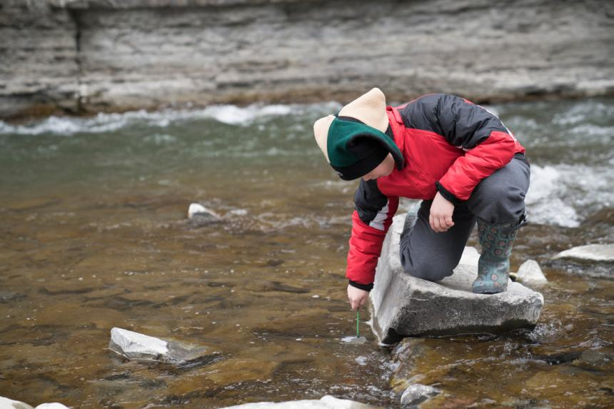 Student kneeling on rock in stream