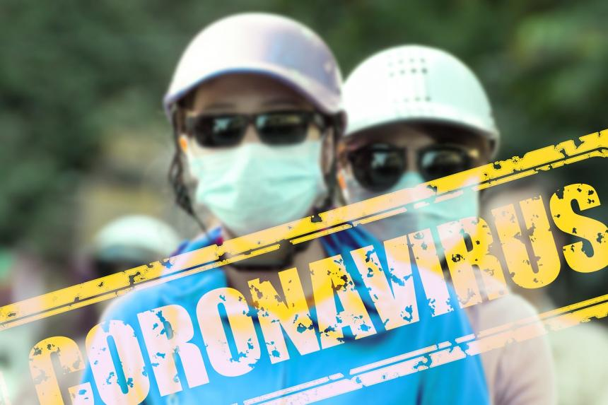 "Two individuals shown with hard hats and masks with the text ""Coronavirus"" juxtaposed over the image of the people"